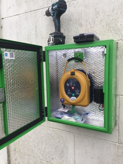 Image of defibrillator open mounted on a stone wall