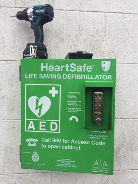 Image of a newly installed defibrillator on a stone wall