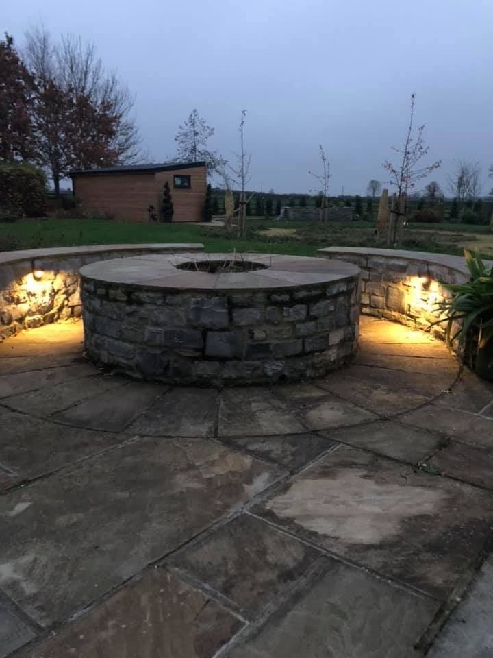 A number of lights installed around a stone fixture illuminating a pathway