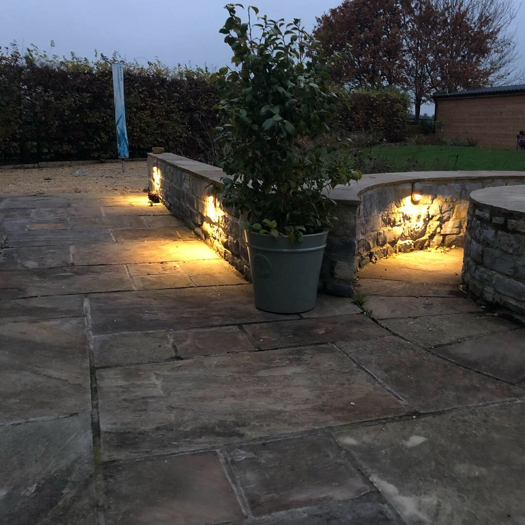 Image of newly installed lighting on a stone walkway in the dark illuminating the path.