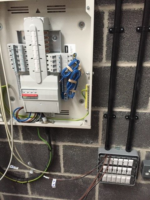 Wiring of a fuse box panel on a wall.